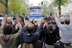 Friedliche Blockade einer Straße durch Demonstranten, die ihre Hände hochhalten - Hamburger Polizisten in Kampfmontur und Wasserwerfer.
