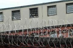 Gefängnismauer mit Stacheldraht - vergitterte Zellenfenster der Hamburger JVA Fuhlsbüttel.