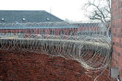 Gefängnismauer mit Stacheldraht - alte Ziegelmauer der Hamburger Justizvollzugsanstalt Fuhlsbüttel - Santa Fu.