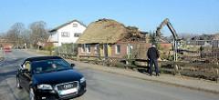 Blick über den Dorfring in Wilstedt - Reste vom Wohnhaus - Kettenbagger / Langfrontbagger bei der Arbeit.