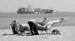 Ein Paar liegt in der Liege am Elbstrand bei Stade in der Sonne - auf der Elbe fährt ein Containerfrachter Richtung Hamburger Hafen.