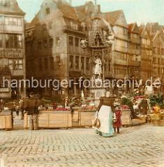 Marktgeschehen auf dem Messberg; Marktfrauen, Bäuerinnen am Marktstand oder hinter Weidenkörben. In der Bildmitte der Vierländer Brunnen, dahinter die Fischerswtiete in der Hamburger Altstadt.