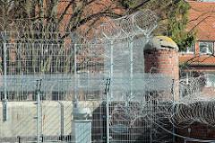 Gefängnismauer mit Gitter und Stacheldraht - alte Ziegelsäule der Hamburger Justizvollzugsanstalt Fuhlsbüttel - Santa Fu.