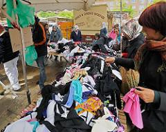 Langer Verkaufstisch mit Kleidung auf dem Wilhelmsburger Wochenmarkt, der zweimal in der Woche auf dem Stübenplatz stattfindet.