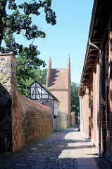 Stadtmauer + Stadttor in Neubrandenburg, schmale Gasse mit Kopfsteinpflaster.