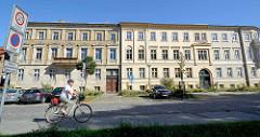 Mehrstöckige Wohnhäuser im Baustil des Klassizismus in Neustrelitz; hälftig restauriert mit neuem Fassadenanstrich,, die andere Hälfte renovierungsbedürftig.