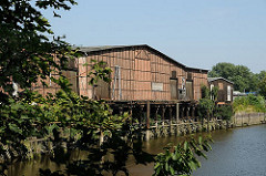 Blick über den Veddeler Marktkanal zu einem historischen Lagerhaus am Ufer des Kanals. Ein Steg und Eisendalben ermöglichten ein Anlegen von Schiffen.