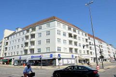 Wohnhaus mit weißer Fassade Balkons, im Erdgeschoss eine Hamburger Drogeriekette;  Architekturbilder aus Hamburg Barmbek Nord