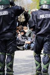 Straßenblockade - Demonstration in Hamburg; Demonstranten geniessen das sonnige Wetter, Polizisten haben Wadenwickel.