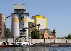 Diamant-Mehl Getreidesilo + Getreidemühle am Reiherstieg - ein Binnenschiff liegt an der Kaimauer; seine Fracht wird über eine Sauganlage gelöscht und in das Silo transportiert.