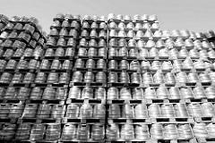 Auf Paletten hoch gestapelte Metallfässer / Bierfässer auf dem Betriebsgelände der Holstenbrauerei in Hamburg Altona, Nord - Schwarz Weiß Fotografie.