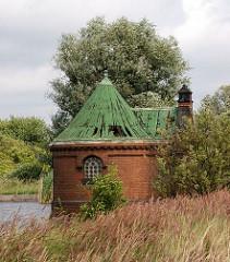 Die Ränder der Filterbecken auf Kaltehofe sind mit dichtem Schilf bewachsen. Teile des Dachs vom zylindrischen Schieberhäuschen sind beschädigt.