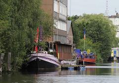 Auf dem Veringkanal liegen bunte Hausboote - die Uferzone ist dicht mit Weiden und Erlen bewachsen; im Hintergrund ist die Spitze des Hamburger Fernsehturms zu erkennen.