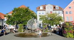 Neuer Markt von Waren - Trinkbrunnen, Bildhauer Walther Preik. Ruhebänke mit BesucherInnen in der Sonne.