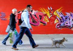 Fussgänger mit Hund unterqueren die Wilhelmsburger Reichsstrasse im Fußgängertunnel - an der Mauer ist ein Graffiti mit Teufel angesprüht.