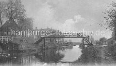 altes Bild vom Ernst-August-Kanal - eine Fussgängerbrücke aus Holz verbindet die beiden Kanalufer; Wege führen am Rand des Kanals entlang,