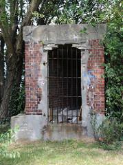 Der alte Eingang zu einem Röhrenbunker in Hamburg Rothenburgsort ist mit einem Gitter versperrt. Dahinter lagert Müll, die Fassade ist mit Schmierereien versehen.