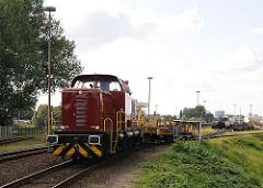 Auf dem Rangierbahnhof von Hamburg Rothenburgsort rangiert eine Güterlokomotive offene Güterwaggons auf den Gleisen.