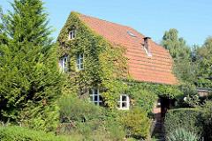 Stadtvilla mit Mansarddach und mit wildem Wein bewachsene Hausfassade;  Wohnhaus in Hamburg Fuhlsbüttel.