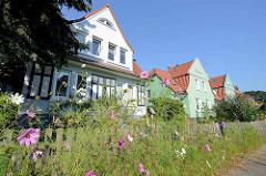 Bunte Straßenblumen im Resedenweg in Hamburg Fuhlsbüttel - schmucke Einzelhäuser mit Holzluken  und farbiger Fassade.