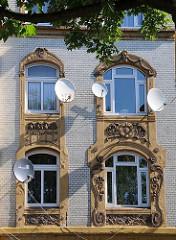 Die Fenster des Wohnhauses in der Wilhelmsburger Strasse Vogelhüttendeich sind mit farblich abgesetzten Jugendstil- Dekoren eingefasst.