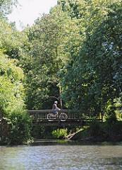 Ein Fahrradfahrer fährt über eine Holzbrücke entlang des Wanderweges am Ufer des Assmannkanals. Das Kanalufer ist mit Bäumen und Büschen dicht bewachsen.