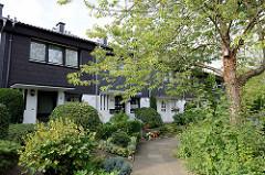 Reihenhäuser mit dunkler Schieferfassade und dicht bewachsen im Vorgarten - Architekturbilder  aus Hamburg Hummelsbüttel.