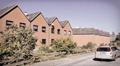 Einstöckige Reihenhäuser mit Spitzdach und Fensterfront zur Straße - im Hintergrund die Seitenansicht baugleicher Wohnhäuser ohne Fenster.