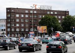 Dichter Autoverkehr auf der Amsinckstrasse - die Fahrzeuge fahren Richtung Billhorner Brückenstrasse / Elbbrücken. Das Wohngebäude mit expressionistische Klinkerfassade.