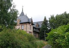 Das ehemalige Labor der Wasserwerke in der Ziegelsteinvilla auf Kaltehofe steht seit Jahren leer. Das Gebäude ist auf der Rückseite mit dichtem Gebüsch und hohen Bäumen bewachsen.