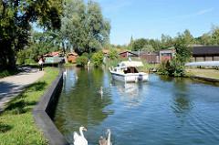 Motorboot im Oberbach in Neubrandenburg - im Hintegrund Bootshäuser.