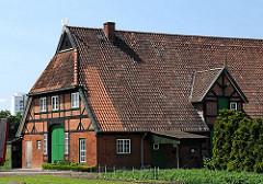 Fachwerkbauernhaus in Hamburg Stillhorn; das Scheunentor ist grün gestrichen auf dem Dachfirst die regionaltypischen sich ansehenden Pferdeköpfe als Giebelschmuck.