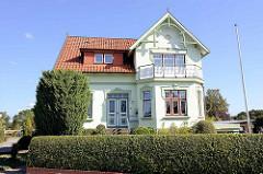 Ländliche Villa aus der Gründerzeit  mit farblich abgesetztem Stuckdekor um Fenster und Türen; Ziergiebel aus Holz.