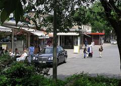 Gäste einer Gaststätte sitzen 2004 auf dem Rothenburgsorter Marktplatz vor dem Laden - Stellschilder stehen auf dem Platz, die Markisen sind gegen die Sonne herunter gelassen.