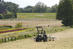 Ein Trecker wendet auf einer Wiese in Hambur Moorwerder das trockene Gras und bereitet es zur Heuernte vor.