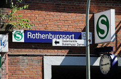 Schild S-Bahn Bahnhof Hamburg Rothenburgsort über dem Eingang - eine Bahnhofsuhr zeigt die Zeit an. Aus dem Mauerwerk des Bahnhofgebäudes wächst ein junge Birke.