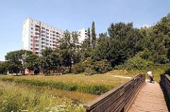 Blick über den Brausielgraben zu einem Hochhaus in der Wohnanlage Kirchdorf-Süd. Bänke stehen an der Wiese.