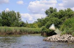 Am Ufer der Süderelbe beim Naturschutzgebiet Heuckenlock steht hohes Schilf bewachsen; Bäume und Sträucher wachsen bis an das Elbufer - Steine befestigen.