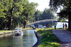 Der Oberbach in Neubrandenburg fließt durch den Kulturpark, eine weite Brücke überquert den Bachlauf.