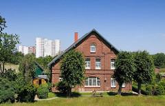 Altes Bauernhaus im Hamburg-Stillhorn am Deich zur Süderelbe - Linden stehen vor dem Ziegelgebäude.