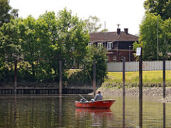Ein Angler ankert mit seinem kleinen Motorboot vor dem Hafen der Bunthäuser Stackmeisterei - er hat zwei Angeln in das auflaufende Wasser der Norderelbe geworfen.