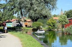 Ein Motorboot fährt im Oberbach von Neubrandenburg Richtung Tollensesee - Spaziergängerin auf dem Fussweg entlang des Wasserlaufs.