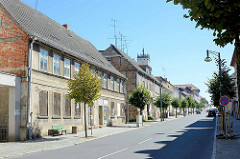 Verlassene Wohnhäuser mit zugenagelten Fenstern, historische Fachwerkarchitektur - junge Straßenbäume / im Hintergrund die Kirchturmspitze.