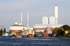 Am Ufer von Kaltehofe in der Billwerder Bucht liegen an einem Anleger Barkassen und Hausboote. Die Abendsonne bescheint das Kraftwerk Tiefstack.
