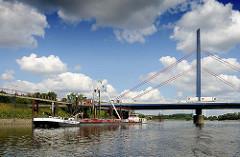 An der Anlegestelle Georgswerder liegt ein Tankschiff und wird über ein Schlauchsystem entladen. Autobahnbrücke mit Polygon und Seile.