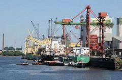 Frachtschiffe liegen an der Reiherstieg - Kaianlage der HaBeMa Futtermittelmühle in Hamburg Wilhelmsburg. Über Krananlagen werden die Massengutfrachter gelöscht.