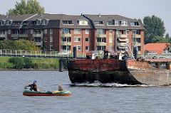 Ein Schubleichter wird von einem Schubschiff über die Billwerder Bucht gefahren; zwei Schiffer stehen am Bug des Schiffs und beobachten das kleine Schlauchboot.