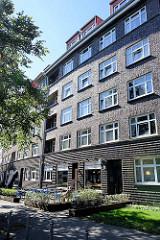Wohnblock mit Klinkerfassade und Straßencafé in der Dithmarscherstraße  in Hamburg Dulsberg.
