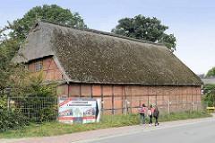 Mit einem Bauzaun abgesperrte alte Fachwerkscheune mit bemoostem Reetdach im Ortskern von Maschen; ein Bauschild weist auf ein neues Bauvorhaben mit zwölf Reihenhäusern hin.