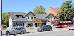 Symmetrisches Doppelhaus - Nutzung für den Einzelhandel, Geschäfte; Autoverkehr  auf der Bramfelder Chaussee in Hamburg Bramfeld.